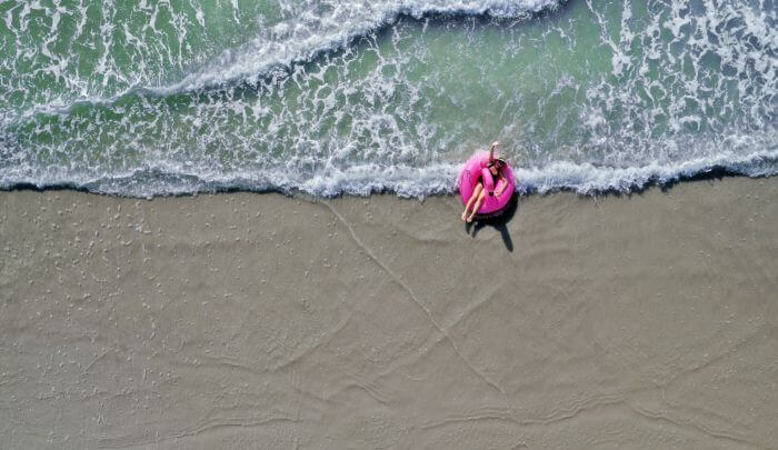 Beach in florida with woman on inflatable.